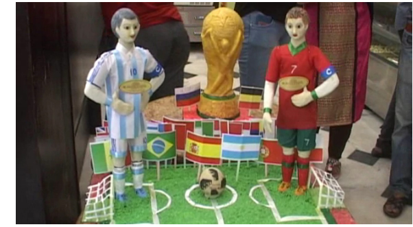 The statues of Lionel Messi, Cristiano Ronaldo and the World Cup trophy made out of sweetmeats at Kolkata