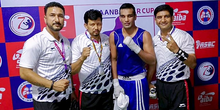Indian boxer Mandeep Jangra (in blue) poses with officials after winning his quarterfinal bout against Batkhuyag Sukhkhuyag in Mongolia, Friday