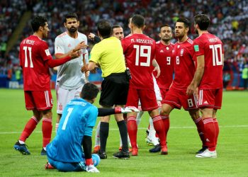 Referee Andres Cunha (in yellow) steps in to diffuse the situation after the alleged stamping 'row' between Diego Costa (in grey) and Iran keeper Ali Beiranvand (in blue)