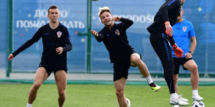 Ivan Rakitic (C) tries to connect a header as teammate Ivan Perisic (L) looks on during Croatia's training session at the Roshchino Arena near St Petersburg