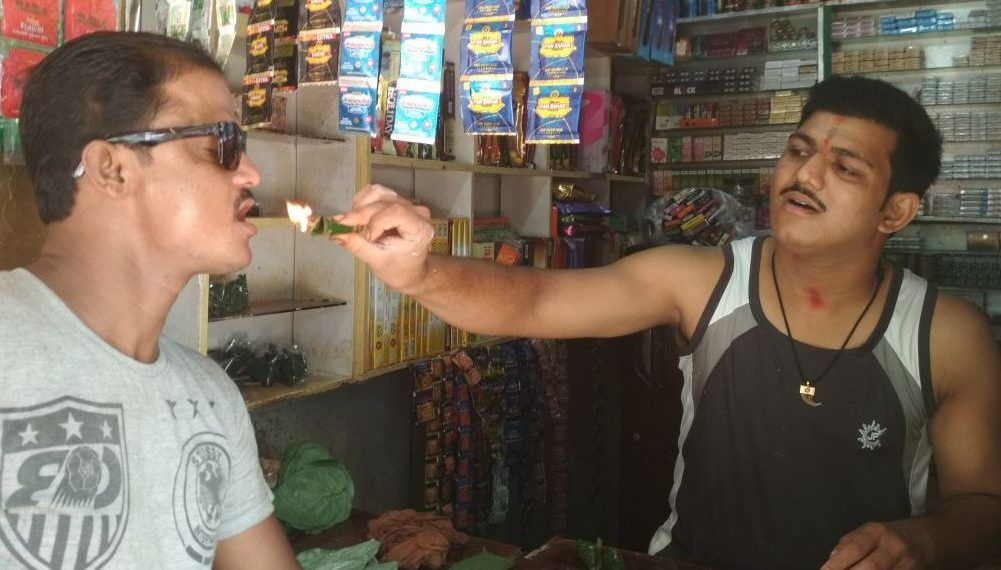 Abhinash Swain helps a customer try a fire paan