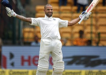 Shikhar Dhawan celebrates his century on the first day of the one-off cricket test match against Afghanistan, at Chinnaswamy Stadium, Thursday