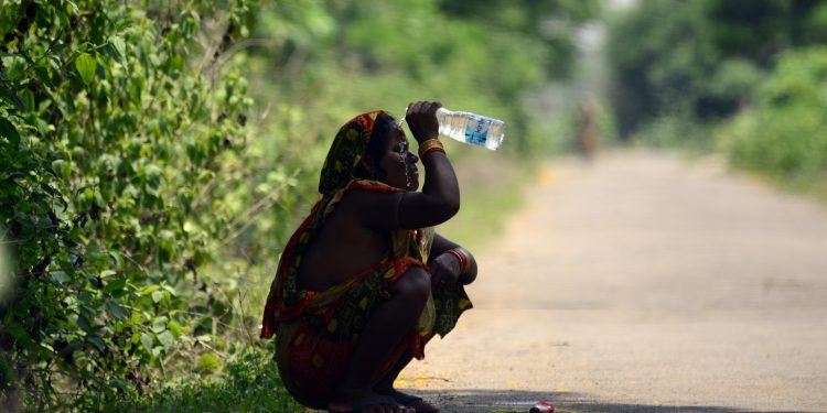 A woman on the outskirts of the city splashes water on her face to get respite from blistering heat Pic: Bikash Nayak