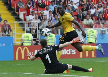 Belgium's Romelu Lukaku tucks the ball past Tunisian goalkeeper Farouk Ben Mustapha to score his side's third goal, Saturday