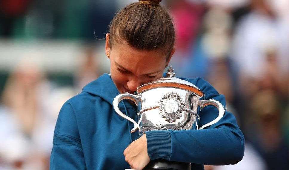 Simona Halep holds tight the Suzanne-Lenglen Cup after winning the French Open women's singles title, Saturday