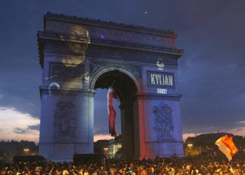 Kylian Mbappe's name is projected onto the Arc de Triomphe in Paris as fans invade the Champs-Elysees Avenue after France's World Cup triumph, Sunday