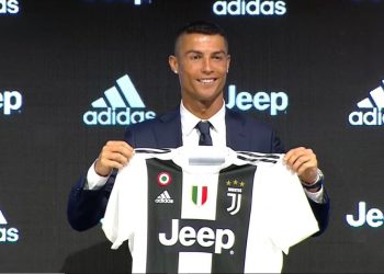 Cristiano Ronaldo poses with his Juventus jersey during his unveiling in Turin, Monday