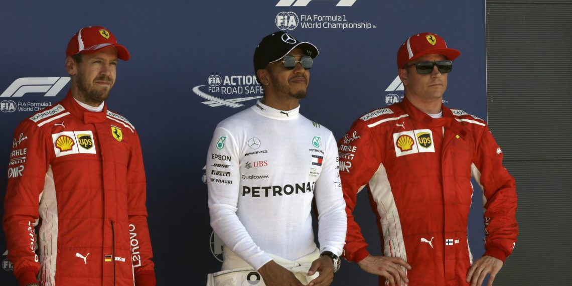 Lewis Hamilton (C) who earned pole position, Ferrari driver Kimi Raikkonen (R) who came in third and teammate Sebastian Vettel who earned the second best time, pose for photos after the qualifying session for the British Grand Prix, at the Silverstone racetrack,Saturday