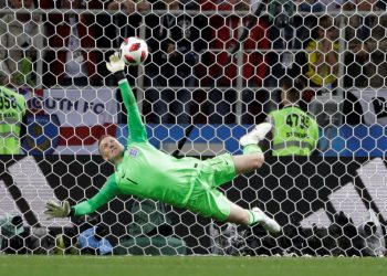 England goalkeeper Jordan Pickford dives to keep out Colombia's Carlos Bacca's shot during the shootout, Tuesday