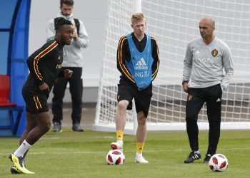 Belgium coach Roberto Martinez R) speaks with Kevin De Bruyne (2nd L) as Michy Batshuayi shoots the ball during their training session, Wednesday