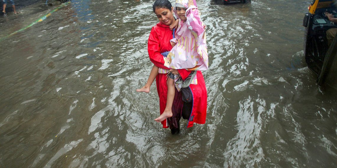 Thane: A woman, carrying a girl, wades through a waterlogged road during heavy rains, in Thane on Monday, July 9, 2018. (PTI Photo) (PTI7_9_2018_000039B)