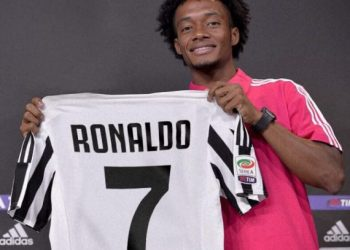 Juan Cuadrado holds the Juventus No.7 shirt which Cristiano Ronaldo will be donning at the club