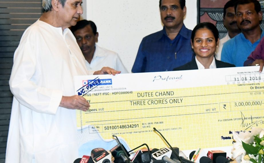 Chief Minister Naveen Patnaik hands a cheque of rupees three crore to Dutee Chand at the state Secretariat