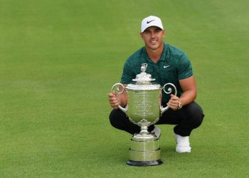 Brooks Koepka poses with the winner's trophy