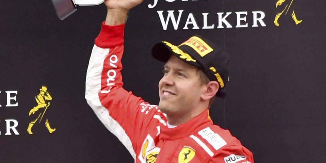 Ferrari driver Sebastian Vettel jubilates with his trophy on the podium after winning the Belgian Grand Prix Spa-Francorchamps