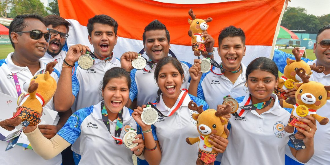 Indian men's and women's archery team members display their silver medals at the Asian Games in Jakarta
