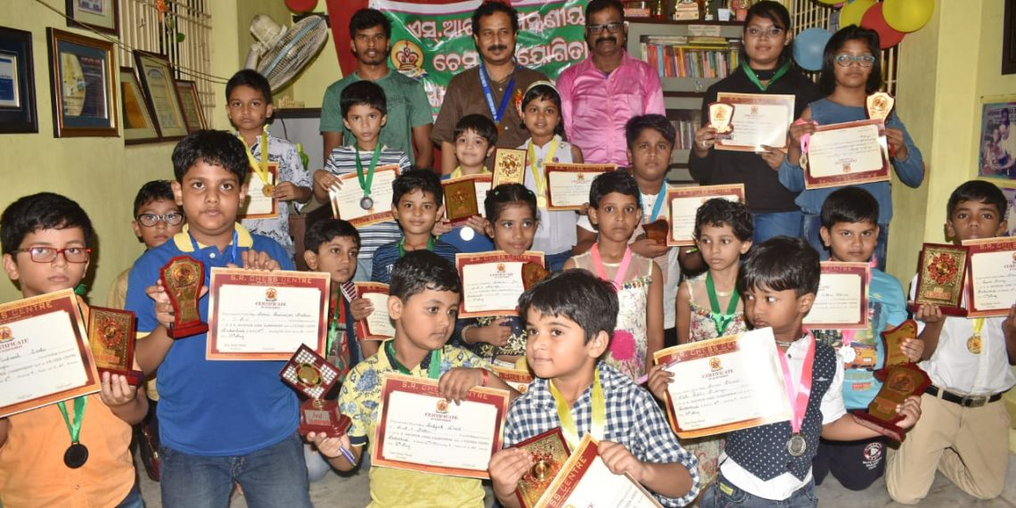 Prize winners of the various categories in the invitational chess tournament pose with their trophies and certificates along with officials at Cuttack, Thursday