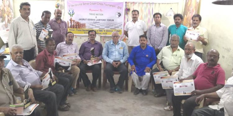 Winners of the Invitational Senior Citizen Chess Championship pose with their trophies and certificates along with guests in Cuttack, Friday