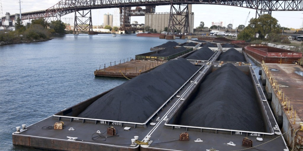 In this Oct. 25, 2013 photo, petroleum coke, or petcoke, is stored on barges on the Calumet River near the Chicago Skyway Bridge in Chicago. The grainy black byproduct of oil refining has been piling up along Midwest shipping channels and sparking a new wave of environmental concerns. The volume and size of petcoke piles has grown sharply _ especially in the Midwest. (AP Photo/Charles Rex Arbogast)