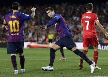 Lionel Messi joins Gerard Pique (C) while the latter wheels away for celebration after scoring Barcelona's equaliser against Girona, Sunday