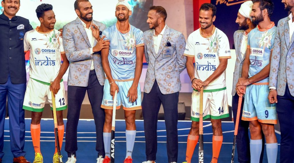 Indian men's hockey team players and coach Harendra Singh (L) during the launch of new home and away kit for the World Cup