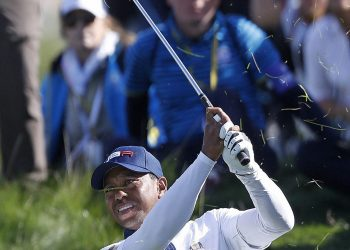 Tiger Woods plays from the rough on the fifth during a foursome match in Paris, Saturday