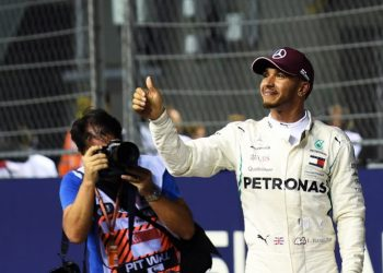 Lewis Hamilton acknowledges the crowd after winning the Singapore Grand Prix at the Marina Bay Street Circuit