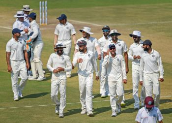 Indian players celebrate their victory over West Indies in their first Test match, in Rajkot
