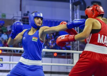 Sonia (in blue) lands punch on his Moroccan opponent Toujani Doaa (in red) during their bout at women's World Championships in New Delhi, Saturday