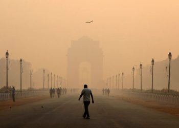 A man walks in front of the India Gate covered in smog.