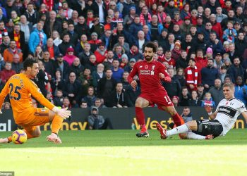 Mo Salah (in red) slots the ball under a hapless Fulham goalie Sergio Rico for Liverpool's opening goal, Sunday