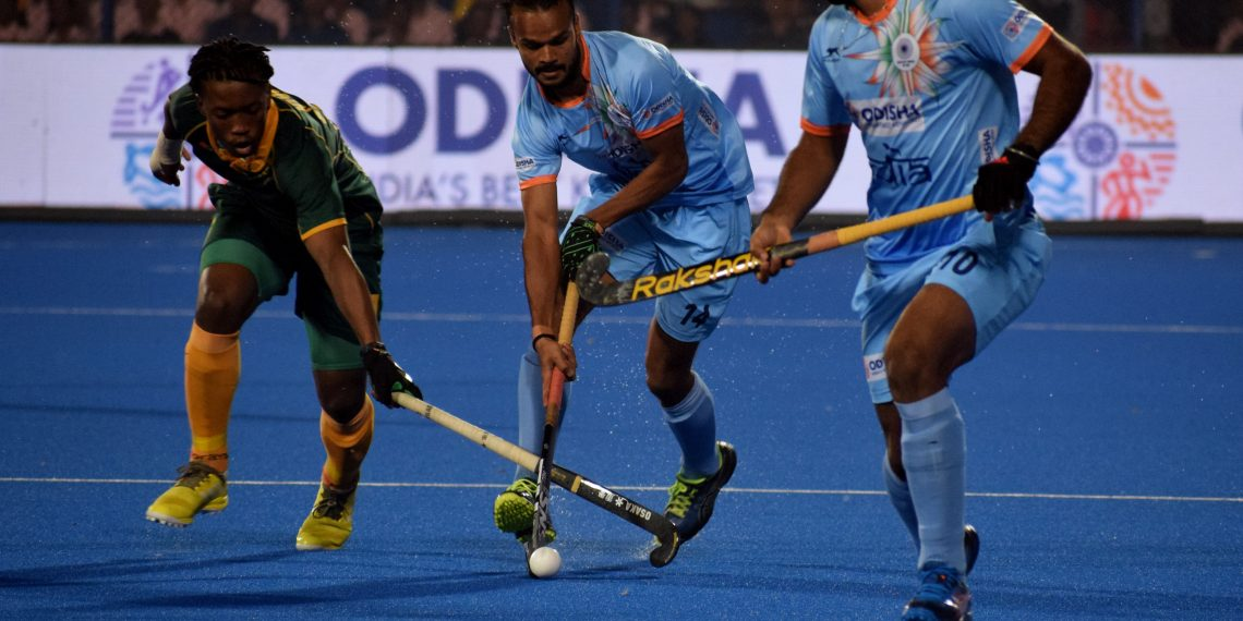 India's Lalit Upadhyay (C) dribbles pasta South African player as another Indian player looks on during their match at the Kalinga Stadium, Wednesday