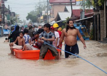 Filipino residents ride on a boat during a rescue operation at a flooded community in the town of Bulan, Sorsogon province, Philippines, Dec. 29, 2018. (AGENCY)