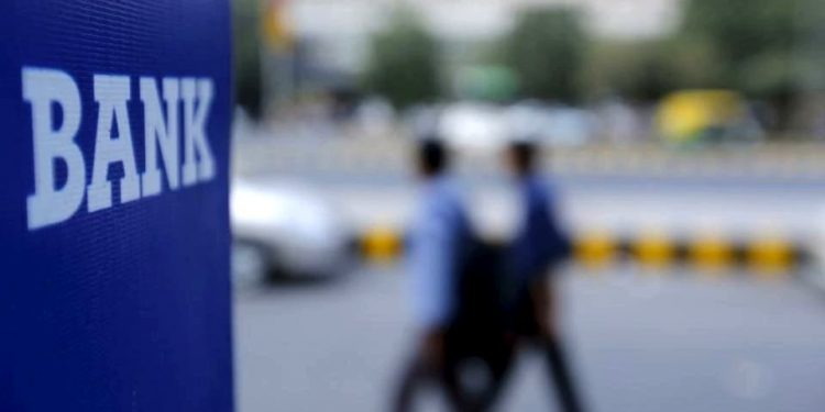 Commuters walk across a bank signage in Delhi (TWITTER)