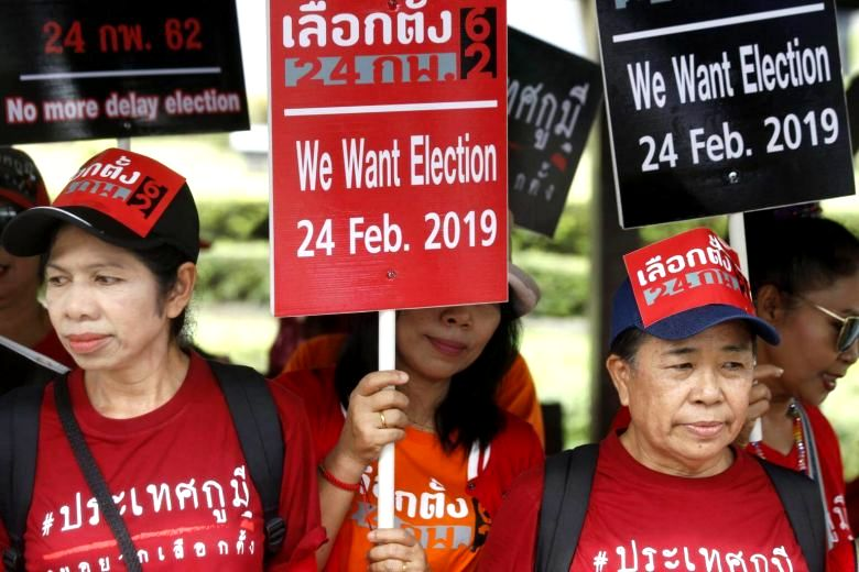 Thai pro-democracy activists hold placards as they gather outside the Royal Thai Army Club