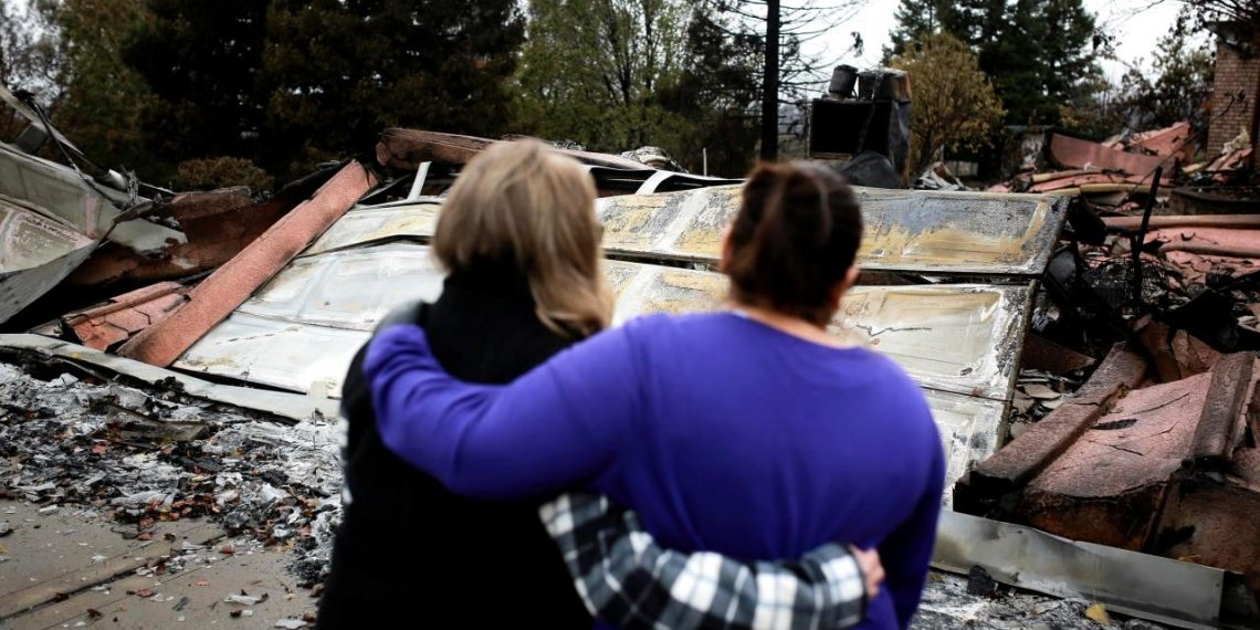 Irma Corona (R) comforts neighbor Gerryann Wulbern in front of the remains of Wulbern's home after the two returned for the first time since the Camp Fire in Paradise, California, U.S. November 22, 2018. (REUTERS)