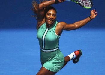 Serena Williams warmed up on Rod Laver Arena in a long, black raincoat which she discarded to reveal a figure-hugging, bottle green one-piece costume paired with fish-net compression stockings. (REUTERS)