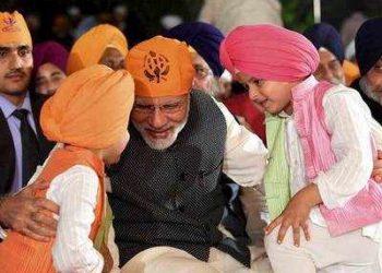 PM Modi interacts with children at a function to mark the birth anniversary of Guru Nanak (PTI)
