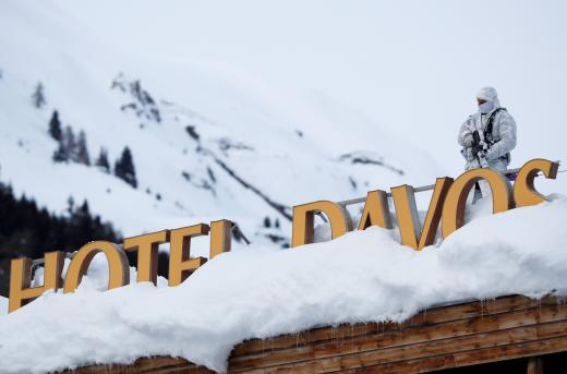 A Swiss police officer observes the surrounding area from atop the roof of the Davos Congress Hotel ahead of the World Economic Forum (WEF) annual meeting in Davos, Switzerland, Monday