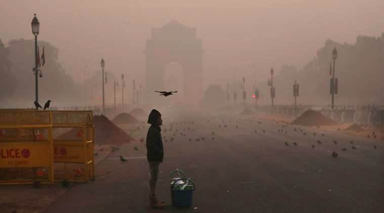 A tea seller boy waits for customers amidst early morning smog around India Gate, the landmark war memorial, in New Delhi, India, Wednesday, Dec. 26, 2018. Air quality in the capital region, already the worst in the world, is hovering between 'severe' to 'poor' category. An ongoing cold wave is worsening the air quality in parts of north India where road, rail and air traffic is also being hit by a dense fog. (AP Photo/Manish Swarup)