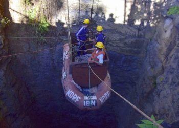 In this photo taken on December 30, 2018, Indian Navy divers go down in the mine with a pulley during rescue operations after 15 miners were trapped by flooding in an illegal coal mine in Ksan village in Meghalaya's East Jaintia Hills district of India. - Indian Navy and NDRF personnel went inside a 370-foot-deep mine, where 15 miners are trapped, to ascertain the water level inside on December 30, officials said. (Photo by - / AFP)