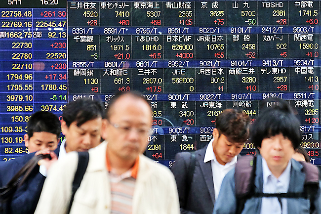 Pedestrians walk past a stock indicator showing stock prices of Japanese companies listed on the Tokyo Stock Exchange in Tokyo on May 11, 2018. Tokyo stocks leapt on May 11, led by rallies in high-tech shares, after Wall Street gains outweighed concern about geopolitical risk over US plans to open an embassy in Jerusalem next week. (AFP PHOTO / Kazuhiro NOGI)