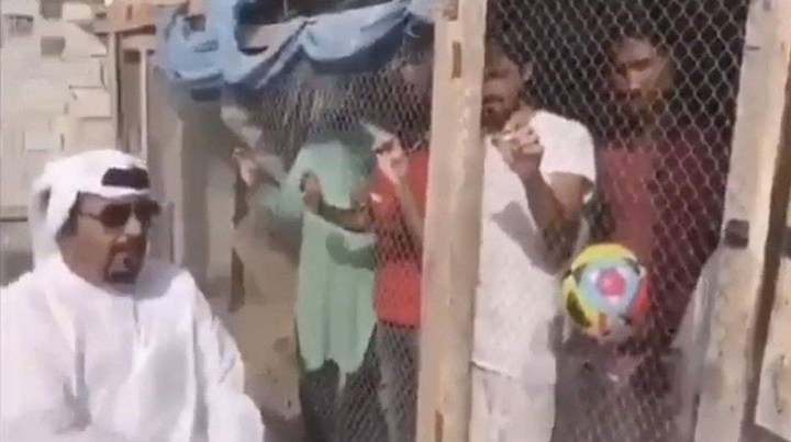 The man poses with Indian fans locked up in a cage with a football
