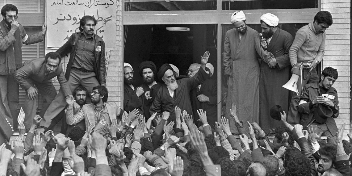 FILE - In this Feb. 1, 1979 file photo, Ayatollah Ruhollah Khomeini, center, waves to followers as he appears on the balcony of his headquarters in Tehran, Iran. Forty years ago, Iran's ruling shah left his nation for the last time and an Islamic Revolution overthrew the vestiges of his caretaker government. The effects of the 1979 revolution, including the takeover of the U.S. Embassy in Tehran and ensuing hostage crisis, reverberate through decades of tense relations between Iran and America. (AP)