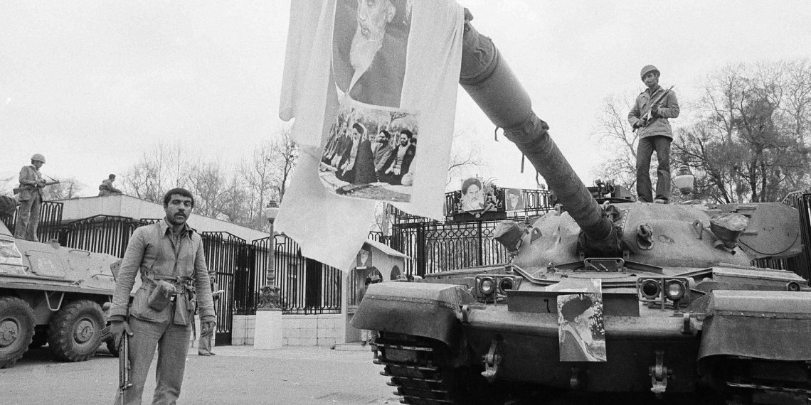 FILE - In this Feb. 13, 1979 file photo, a large picture of Ayatollah Khomeini hangs from tank gun barrel in front of Niavaran Palace in Tehran, Iran. Forty years ago, Iran's ruling shah left his nation for the last time and an Islamic Revolution overthrew the vestiges of his caretaker government. The effects of the 1979 revolution, including the takeover of the U.S. Embassy in Tehran and ensuing hostage crisis, reverberate through decades of tense relations between Iran and America. (AP)