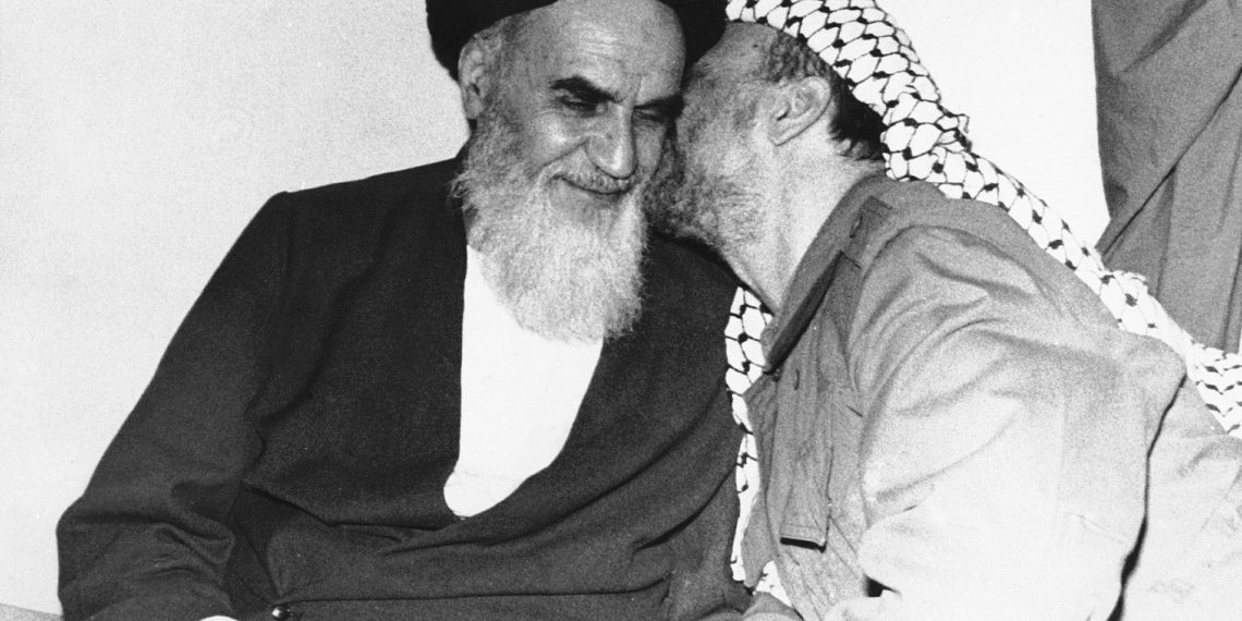 FILE - In this Feb. 18, 1979 file photo, Palestinian Liberation Organization leader Yasser Arafat, right, kisses Ayatollah Ruhollah Khomeini, left, during a meeting in Tehran, Iran. Forty years ago, Iran's ruling shah left his nation for the last time and an Islamic Revolution overthrew the vestiges of his caretaker government. The effects of the 1979 revolution, including the takeover of the U.S. Embassy in Tehran and ensuing hostage crisis, reverberate through decades of tense relations between Iran and America. (AP)