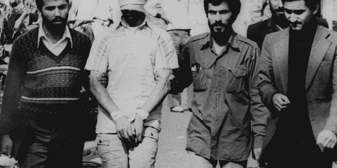 FILE - In this Nov. 9, 1979 file photo, one of the hostages seized when Islamic radicals stormed the U.S. Embassy in Tehran, blindfolded and with his hands bound, is displayed to a crowd in Tehran, Iran. Forty years ago, Iran's ruling shah left his nation for the last time and an Islamic Revolution overthrew the vestiges of his caretaker government. The effects of the 1979 revolution, including the takeover of the U.S. Embassy in Tehran and ensuing hostage crisis, reverberate through decades of tense relations between Iran and America. (AP)