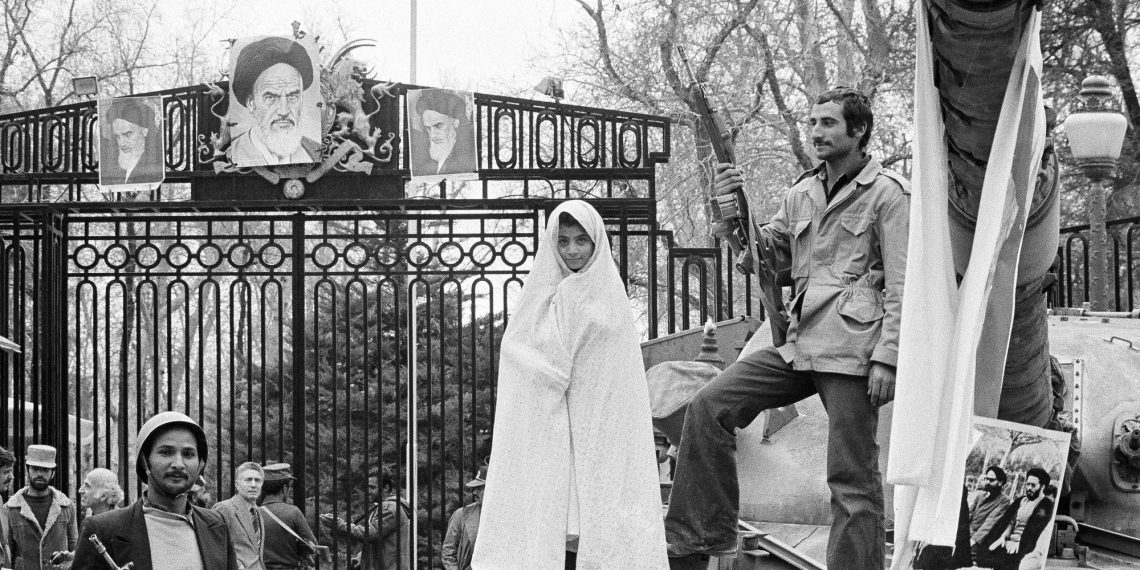 FILE - In this undated photo from 1979, a small Iranian girl stands on a captured tank at the entrance to Niavaran Palace where Shah Mohammad Reza Pahlavi once lived in Tehran, Iran. Forty years ago, Iran's ruling shah left his nation for the last time and an Islamic Revolution overthrew the vestiges of his caretaker government. The effects of the 1979 revolution, including the takeover of the U.S. Embassy in Tehran and ensuing hostage crisis, reverberate through decades of tense relations between Iran and America. (AP)