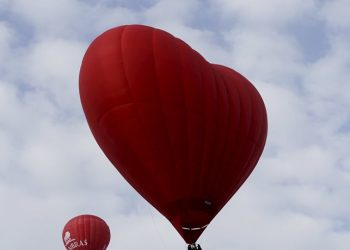 A heart shaped hot-air balloon (R) flies in the sky during the Love Cup 2016 event, ahead of Valentine's Day, in Jekabpils, Lativa, February 13, 2016 (REUTERS)