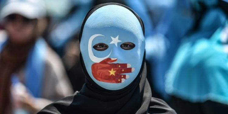 A demonstrator wears a mask with the colors of the East Turkestan flag and a hand depicting the Chinese flag to protest Beijing's treatment of Uighurs outside China's consulate in Istanbul in July 2018 (AFP)